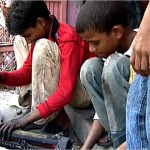 Two young boys dismantle printers, with no protective gear or equipment.