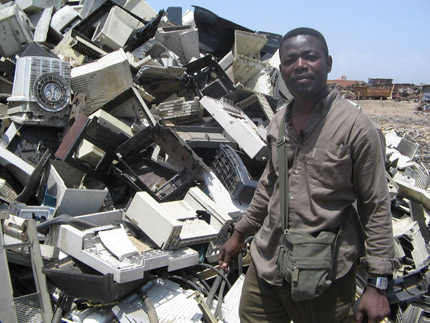 Mike Anana standing next to a pile of e-waste (Credit: Mike Anana)