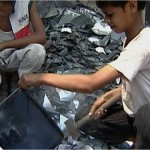 A young boy named Danish sits atop a pile of electronic scraps and glass breaking apart monitors and televisions without any protection.