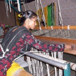 A woman in Delhi, India, uses a loom to create handbags from old plastic bags. The waste picker's wives take plastic bags (shown hanging in the background) and weave them into handbags at Metamorphosis.